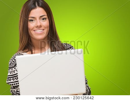 Young Woman Holding Laptop against a green background