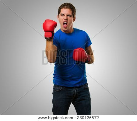 Aggressive Man Wearing Boxing Gloves against a grey background