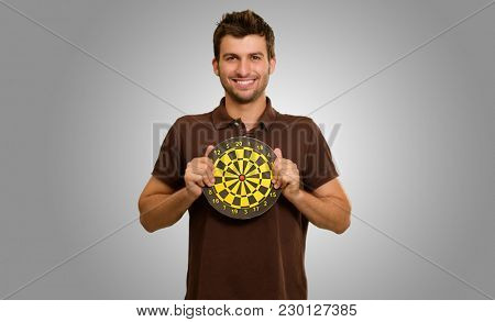 Portrait Of A Man Holding A Dartboard On Grey Background