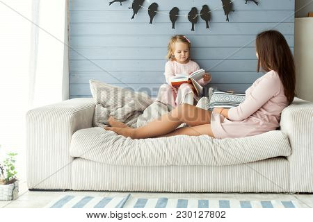 Mom And Daughter Are Sitting On The Sofa By The Window. Daughter Reading A Book.