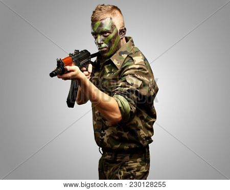Portrait Of A Soldier Aiming With Gun against a grey background