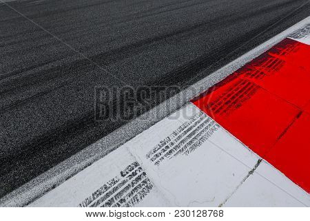 Asphalt Red And White Kerb Of A Race Track Detail With Tire Marks