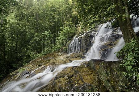 Stunning Waterfall Flow From The Hill, Wet Rocks And Green Mossy. Surrounded By Nature