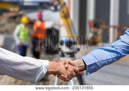 Two Business People Shaking Hands In Front Of Leveling Instrument On Construction Site With Workers