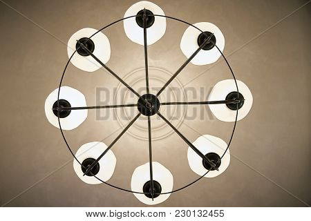 A Glowing Chandelier With Transparent Flacons Close-up Hanging On The Ceiling.