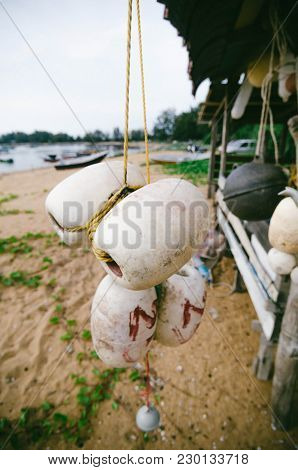 Blurred And Selective Focus Image Of Hanging White Dirty Fish Net Buoy Tied Together With Yellow Rop