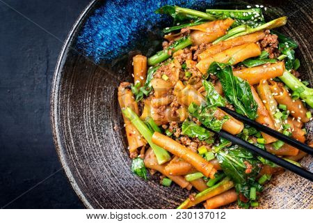 Thai Pad See Ew Noodles with vegetable and minced beef as close-up in a bowl with copy space