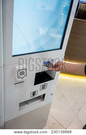 Hand Inserting Card Into The Tax Refund Kiosk