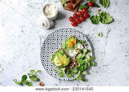 Vegetarian Sandwiches With Avocado, Ricotta, Egg Yolk, Spinach, Cherry Tomatoes On Whole Grain Toast