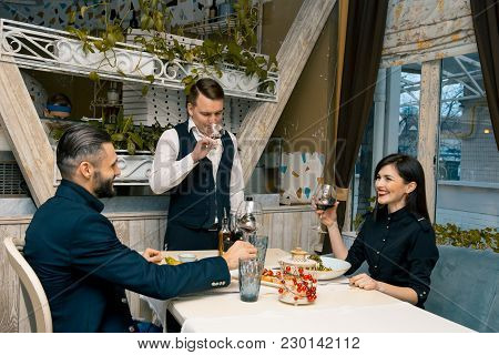 Couple Enjoying A Romantic Meal Together. Sommelier Presents And Digests Wine At The Restaurant