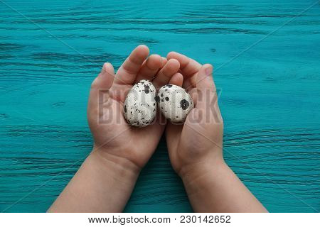 Two Eggs In The Palms Of A Child On A Wooden Background