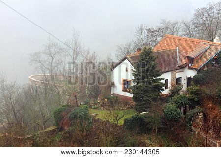 Small Cozy House With A Tile Roof On The Steep Bank Of The Thaya River, Covered With Fog. Znojmo, Cz