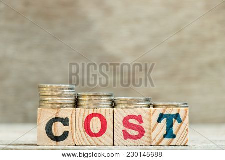 Block In Word Cost With Coin In Down Trend On Wood Background