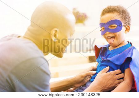 Happy Smiling African American Son Being Supported And Helped By Supportive Father For Little Advent