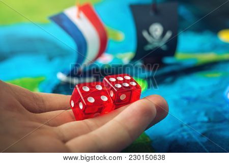 Hand Throwing Red Dice On The World Map Of The Playing Field Handmade Board Games With A Pirate Ship
