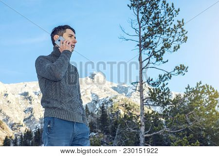 Young Man In A Sweater With Phone In Hand On The Snowy Mountain. Concept Availability Of Mobile Conn