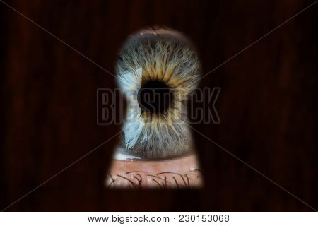 Male Blue Eye Looking Through The Keyhole. Concept Of Voyeurism, Curiosity, Stalker, Surveillance An