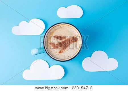 Cup Of Cappuccino With A Picture Of The Plane On The Foam. Blue Sky Background With Paper Clouds. Co
