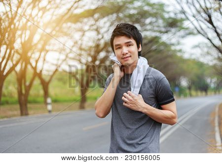 Young Sporty Man Resting And Wiping His Sweat With A Towel After Workout Sport Exercises Outdoors At