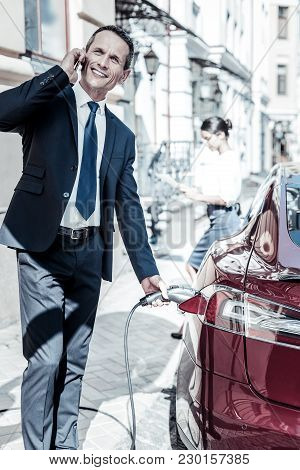 Absolutely Busy. Nice Handsome Busy Man Standing Near His Car And Refilling It While Having A Phone