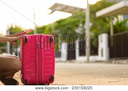 Beautiful Traveler Asian Woman Sitting On The Street With Big Pink Bag For Waiting Taxi Driver Servi