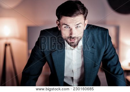 Its Me. Serious Perspective Stylish Man Standing In The Specious Room Tilting His Body And Looking S