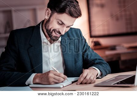 Funny Notes. Pleasant Satisfied Unshaken Man Sitting By His Desktop Smiling And Writing In His Noteb