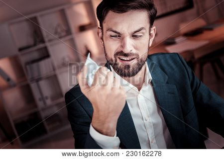 Bad Things. Angry Dissatisfied Unshaken Worker Sitting In The Office Holding And Minting The Documen
