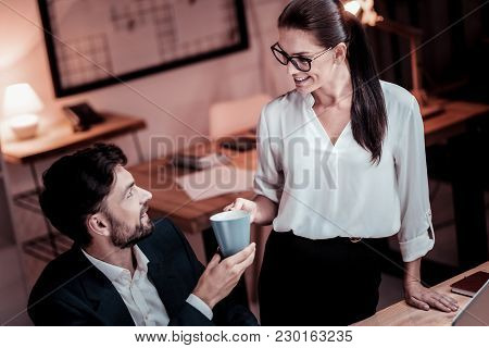 Have A Rest. Pleasant Bespectacled Pretty Employee Standing In The Office Giving A Cup Of Tea Her Co