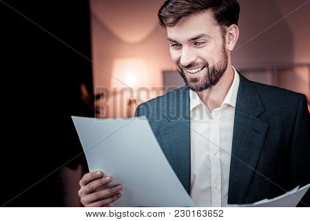 Important Document. Interested Smart Satisfied Worker Standing In The Specious Room Smiling And Read
