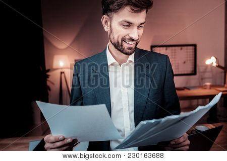 Paper Work. Responsible Skilled Pleasant Employee Standing In The Cabinet Smiling And Overlooking Do