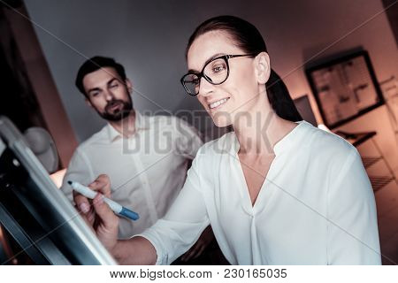 Its My Project. Occupied Joyful Bespectacled Woman Standing In The Office Smiling And Writing On The