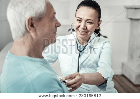 One More Time. Senior Pleasant Aged Man Sitting At Home In The White Bright Room Doing Nurses Orders