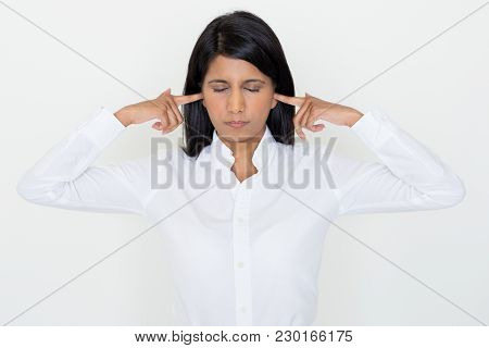 Closeup Portrait Of Annoyed Beautiful Dark-haired Woman Stopping Ears With Fingers With Her Eyes Clo