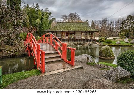 Red Arch Bridge In Public Japanese Garden In Toulouse, France