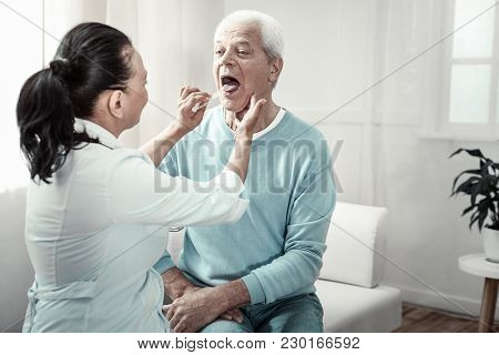 Show Your Tongue. Senior Grey Haired Pleasant Man Sitting On The Sofa Having Medical Examination And