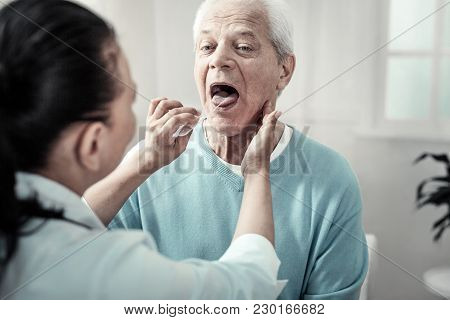 Sore Throat. Serious Aged Concentrated Man Sitting Opposite The Nurse Showing His Tongue And Doing N