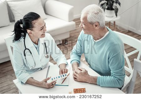 Weekly Stock. Mature Cute Joyful Nurse Sitting By The Table With Her Patient Giving Pills To Him And
