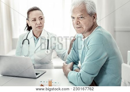 Bad News. Serious Deep Aged Man Sitting In The Room By The Table With The Nurse Thinking About Docto