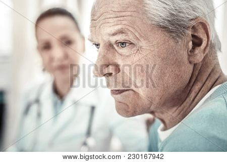 Health Problems. Thoughtful Aged Deep Man Sitting In The Room Near The Doctor Concentrating On His T