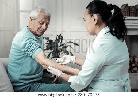 It Does Not Hurt. Aged Pleasant Kind Man Sitting In The Room Near The Nurse Having Injection And Spe