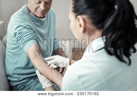 Hygienic Standards. Aged Senior Pleasant Patient Sitting Near The Nurse Having Injection And Trustin