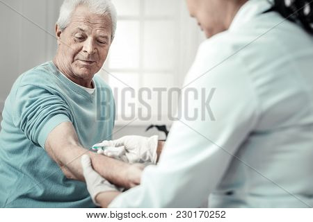 One More Injection. Sick Aged Senior Man Sitting In The Bright Room With The Nurse Looking At His Ar