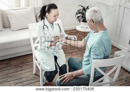 Do Not Move. Concentrated Serious Skilled Nurse Sitting Opposite Her Patient Keeping Calm And Making
