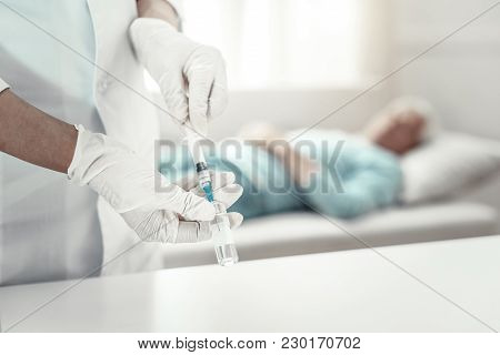 Correct Dose. Reliable Skilled Concentrated Nurse Standing Near The Table Keeping Syringe And Dosing