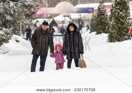 Saratov / Russia - March 8, 2018: Grandparents And Granddaughter Walking In The City Park. Winter Da
