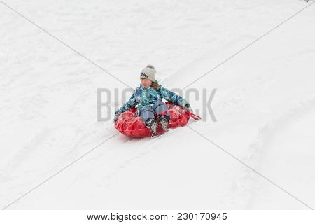 Saratov / Russia - March 8, 2018: Children Ride With An Ice Slide. Winter Vacation. Outdoor Activity