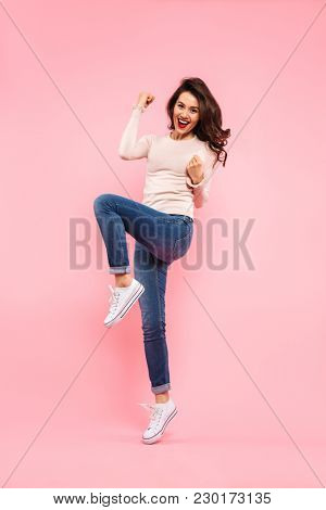 Full-length portrait of cheerful woman having long dark hair celebrating victory with clenching fists isolated over pink background