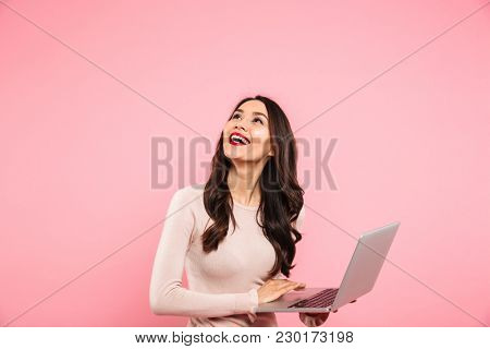 Photo of brunette cute woman in casual sweater holding silver notebook and looking upward on copyspace with candid smile isolated over pink background