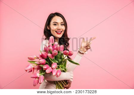 Charming brunette female holding amazing bunch of blossom tulips on women's day and pointing finger on copyspace isolated over pink background